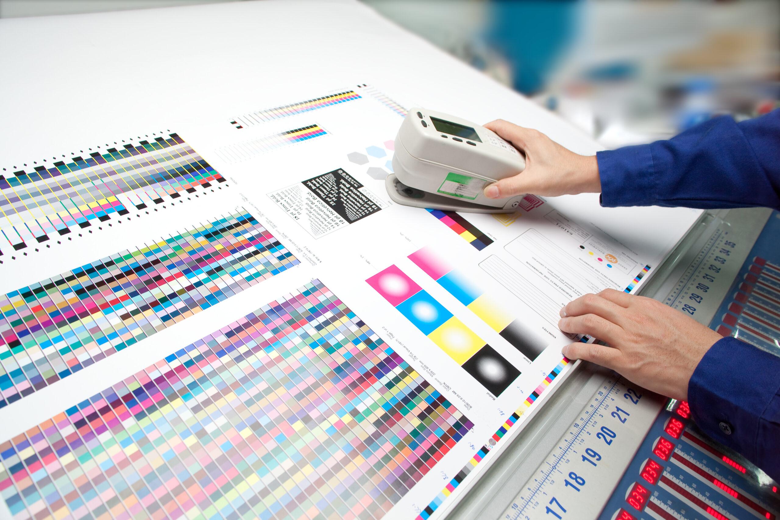 オフセット印刷色見台で測色する作業者の手